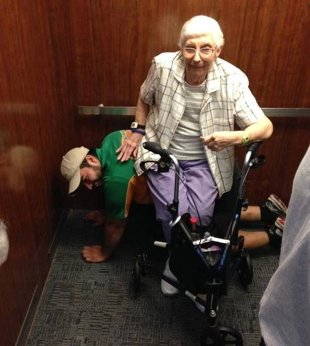 Man lets elderly lady sit on him when stuck in elevator
